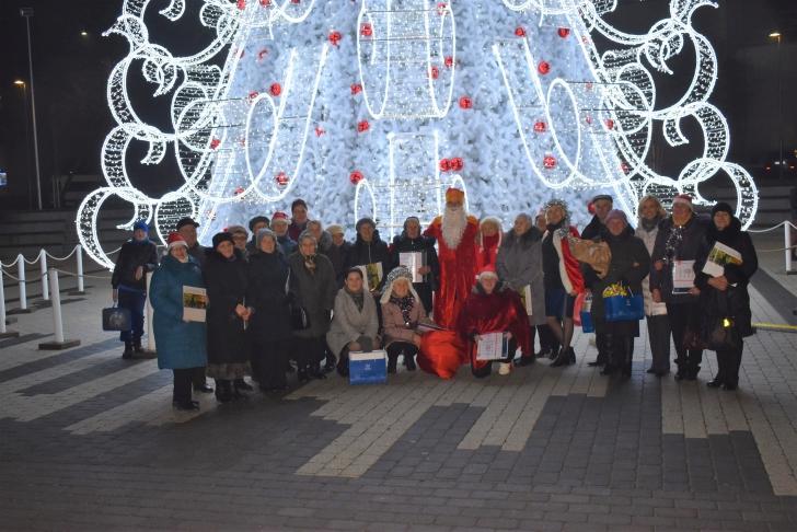 """Bendruomenės """"Upė"""" narių nuotrauka prie Širvintų Kalėdų eglės."""