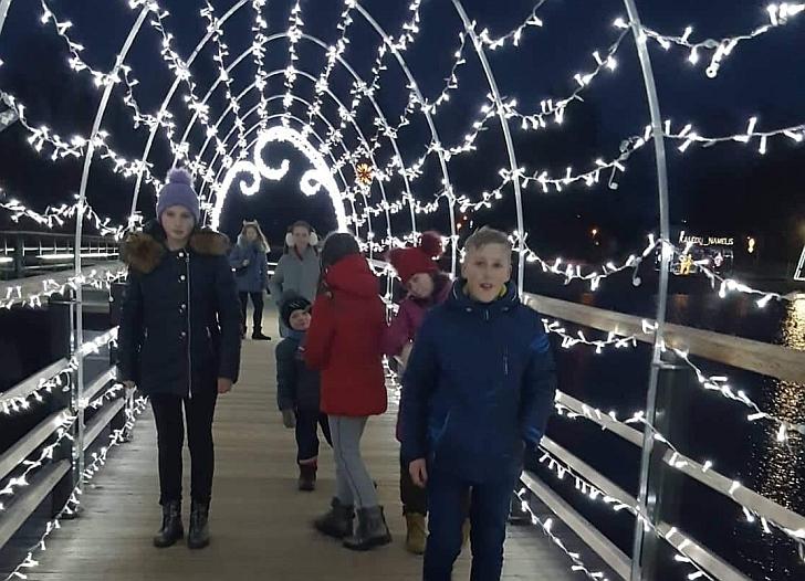 Ant šventiškai išpuošto pėsčiųjų tilto.