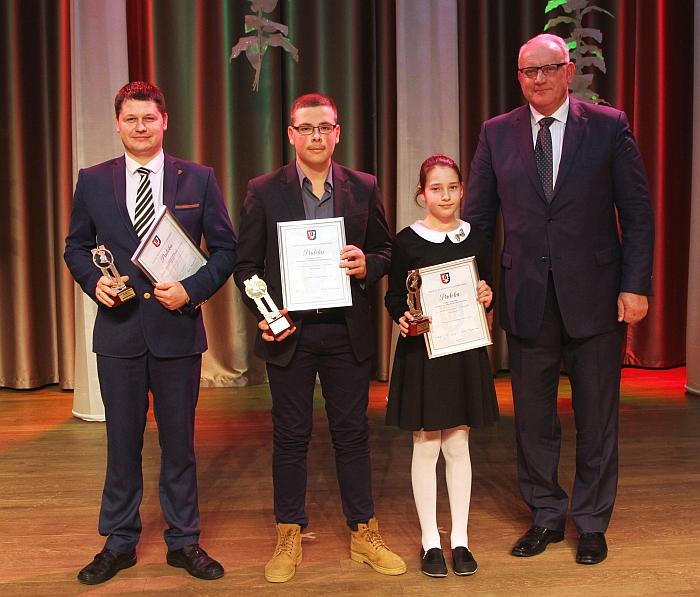 Gintautas Igliukas su mokiniais, kurie pripažinti geriausiais plaukikais: Martynas Valavičius ir Gintarė Sadūnaitė ir jiems apdovanojimą įteikusiu. Juos sveikino Jonas Pinskus.
