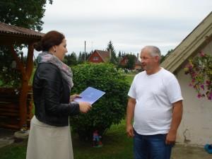 Merės padėjėja Janina Greiciūnaitė įteikia merės padėką Algiui Šalkauskui už gražiai tvarkomą sodybą.