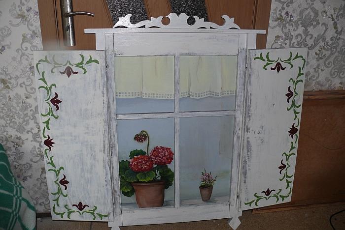 Senas trobos langas su langinėmis, ant palangės stovi pelargonija. Čia tik piešinys ant medžio.