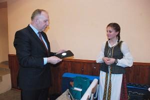 Vyriausybės kanclerio pirmasis pavaduotojas Remigijus Motuzas už teisingą atsakymą devintokei Justinai Rakauskaitei dovanoja stilingą atšvaitą.