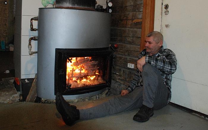 Aleksandras Besonovas savo namuose prie savos konstrukcijos katilo su židiniu.