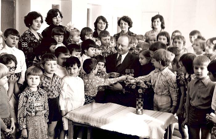 Darželio ugdytinių susitikimas su karo dalyviu Stanislovu Dačka (už vaikų pirma iš kairės stovi darželio vedėja Veronika Sprogienė, antra - muzikos vadovė Zina Stonienė). 1980 m.