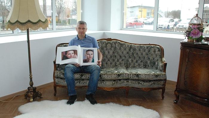 Fotografas Arturas Gerulskis namus primenančiame interjere su nuostabių nuotraukų albumu rankose.