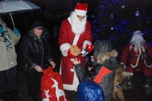 Kalėdų Senis vaikams dalija dovanas.
