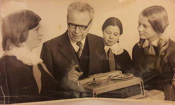 """Juodiškių mokyklos kraštotyrininkės (iš kairės į dešinę) Gražina Vaivadaitė-Potanina, Janina Misiūnaitė-Ošenienė ir Danutė Savanevičiūtė-Audėjienė su lietuvių kalbos mokytoju Viktoru Alekna. 1974 m. Klausomasi įrašo per gamybiniame susivienijime ELFA pagamintą lietuvišką dviejų garso takelių juostinį magnetofoną """"Daina""""."""