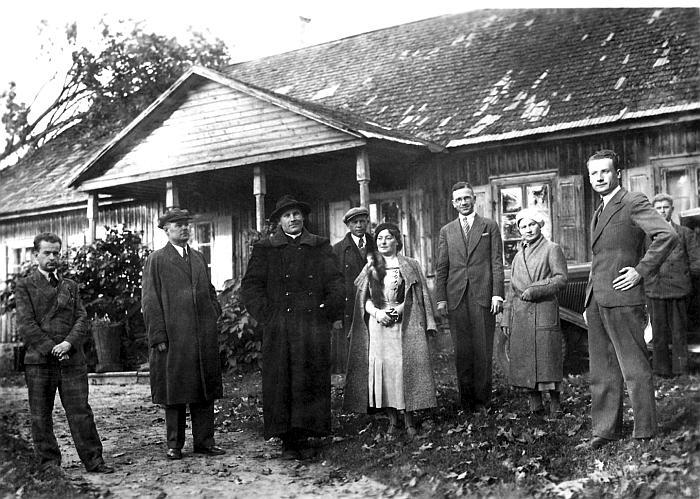 Kunigas Nikodemas Švogžlys su svečiais prie senosios klebonijos pastato (dabar - Bažnyčios reliktų muziejus). Valstybinio Kernavės kultūrinio rezervato direkcijos archyvas.