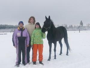 Gimtojo hipodromo fone Didžiųjų ristūnų žirgų lenktynių Sartuose dalyviai. Iš kairės į dešinę: Kipras Varaneckas, Diana Kvakšytė, Juozas Kvakšys ir žirgas Gajus.