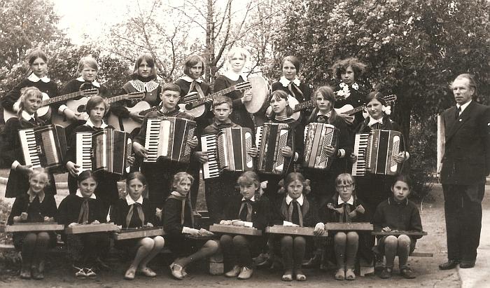 Zibalų aštuonmetės mokyklos orkestras: (pirmoje eilėje sėdi iš kairės į dešinę) Roma Šikšnytė, Virginija Skorupskaitė, Virginija Maslinskaitė, Vida Kriaučiūnaitė, Danguolė Martinėlytė, Irena Andrikonytė, Laima Gudeikytė, Gražina Pivoraitė, (antroje eilėje iš kairės į dešinę) Asta Vinslauskaitė, Aldona Dasevičiūtė, Algis Kasinskas, Donatas Didžiokas, Dalia Kiškytė, Regina Burlėgaitė, Melanija Matulytė, (trečioje eilėje iš kairės į dešinę) Mikalina Latvytė, Danutė Jackūnaitė, Ona Raišytė, Audronė Lajauskaitė, Stasė Kapcevičiūtė, Zita Dikaitė, Aldona Kapcevičiūtė. Dešinėje stovi mokytojas Viktoras Kiškis. 1973 m.