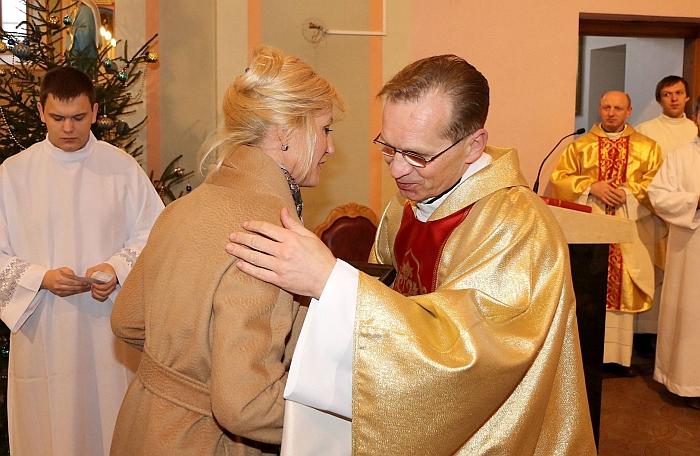 Merė Živilė Pinskuvienė sveikina kunigą dekaną Leoną Klimą.