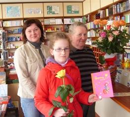 Jaunoji pirkėja, išsirinkusi patikusią knygą, buvo maloniai nustebinta - Knygyno direktorė Vaiva Daugėlienė ir ilgametė darbuotoja Stasė Stuklinskienė jai už tai padėkojo ir padovanojo rožę.