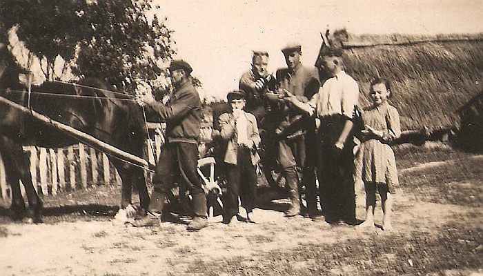 """Melioratoriai, vadinami """"zimagorais"""", Limonių kaimo gyventojo Stasio Šikšnio (pirmas iš kairės) kieme. Arklių traukiamuose vežimuose buvo vežiojami melioracijos vamzdeliai."""