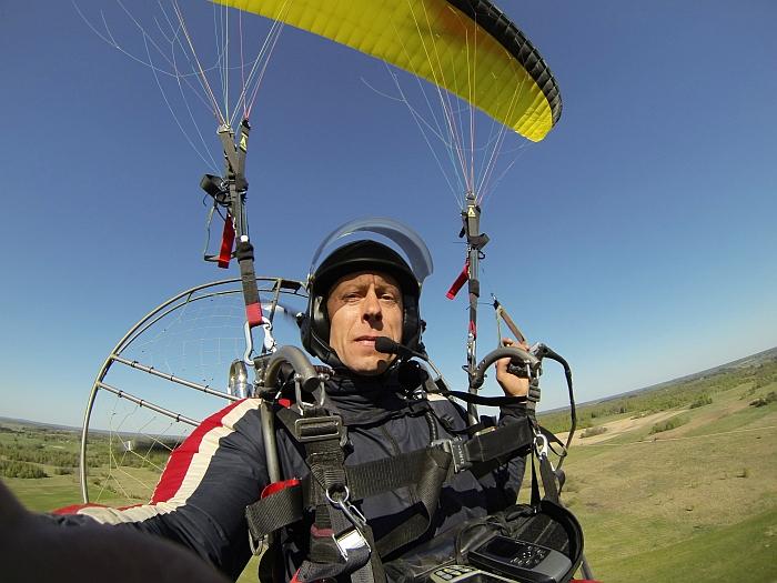 Darius Paliukėnas ore. Už nugaros - propeleris, o virš galvos - sparnas.