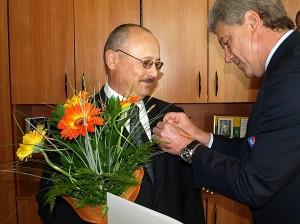 """Leonardas Čaikauskas Romualdui Chmeliauskui įteikė medalį """"Už nuopelnus Lietuvos sportui""""."""