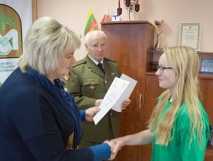 """Širvintų """"Atžalyno"""" progimnazijos direktorė D. Klimienė apdovanoja pirmosios vietos nugalėtoją Adriją Redeckaitę."""