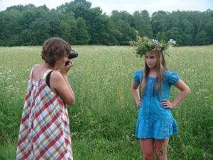 Fotosesija. Fotografuoja mokytoja Rasa. Su vainikėliu ant galvos pozuoja Kamilė.
