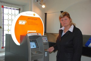 """""""Swedbank"""" padalinio Širvintose valdytoja Daiva Vencevičienė rodo, kaip grynieji pinigai įnešami į sąskaitą per pinigus priimantį automatą."""
