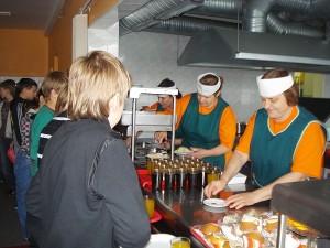 Kai prie prekystalio nutįsta didžiulė norinčiųjų skaniai ir sočiai pavalgyti eilė, valgykloje dirbančios moterys vos spėja suktis.