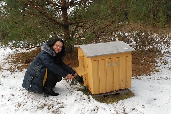 Bitininkė tikrina avilį, kaip bitelės žiemoja.