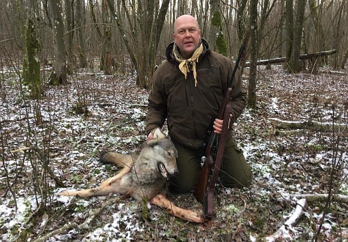 Audrius Valaiša pagal medžiotojų tradicijas priklaupęs atiduoda pagarbą sumedžiotam vilkui.