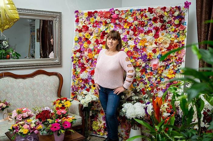 Žaneta Gerulskienė savo gėlių salone prie gėlėmis nusėto stendo.